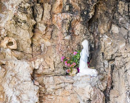 menorca: statue of a kneeling virgin in a sanctuary menorca Stock Photo