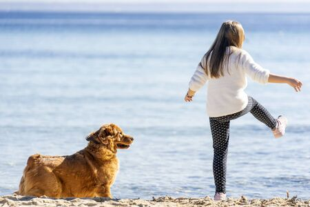 little girl playing with a dog on the beach