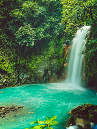 Waterfall in tropical forest, blue water.