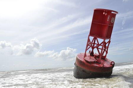 Red buoy ringed on the beach after a hurricane
