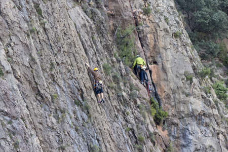 Men climbing the vertical walls of the dam of Escales, Spain