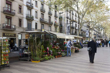BARCELONA - NOVEMBER 07: Tourists and typical flower kiosks in the Ramblas of Barcelona on nov 7TH 2011 in Barcelona, Spain