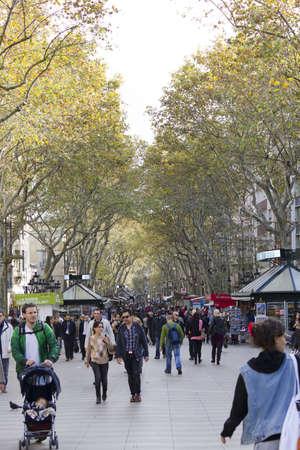 BARCELONA - NOVEMBER 07: Tourists stroll by The Ramblas of Barcelona on nov 7TH 2011 in Barcelona, Spain