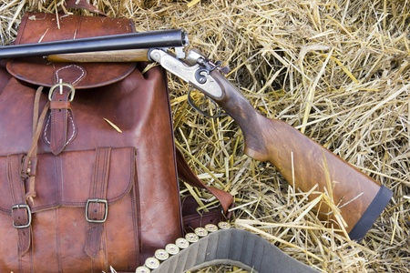 Shotgun, backpack leather bandolier of cartridges in the field