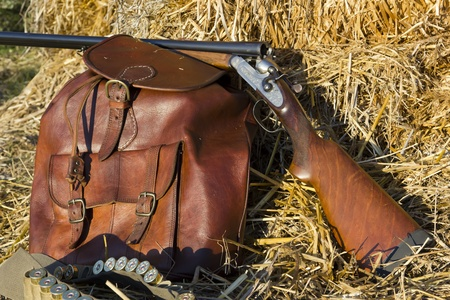 A shotgun and a backpack in the field to hunt Stock Photo