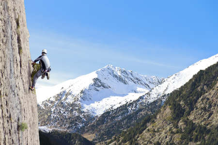 A man climbing a wall with magnificent views of snowy mountains Stock Photo