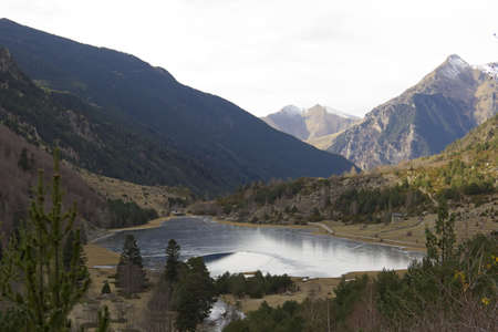 High mountain lake ice and reflection of the mountains, National Park and Lake Aigüestortes St. Maurice in the Spanish Pyrenees