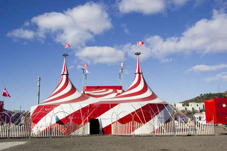 Large red and white tent of the Circus, and blue sky