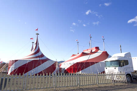 Red and white tent of the Circus, white fence and trucks