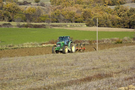A tractor tilling the soil for planting in the field