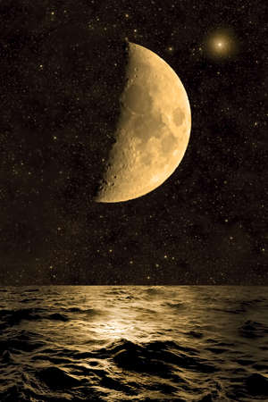 Crescent moon rising over the sea Stock Photo
