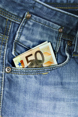 Very closely in foreground the back of jeans, with money  in the pocket photo