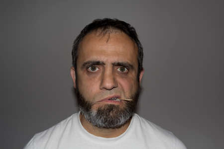 A man a beard but no mustache, looking dangerous and a toothpick in his mouth Stock Photo