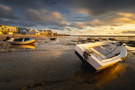 Beautiful sunset on the beach of La Caleta when the tide goes down and the boats that remain static Banco de Imagens