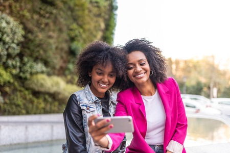 Afro American Young Mother Taking a Selfie with her Daughter Outdoors . Separated Mother Spending Time with her Daughter . Latin American Girls Having Fun. Family Concept.