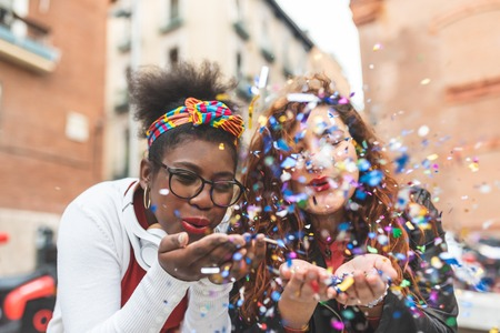 Latin American Girls Playing with Confetti in the Street. Afro American and Red Hair Girl Blowing Confetti Outdoors. Friends Having Fun. Youth Concept.