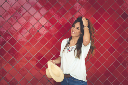 Girl posing with a hat in front of a red wall. She has the hat in her hand. She wears red pants and a white t-shirt. Horizontal photo with space on the right