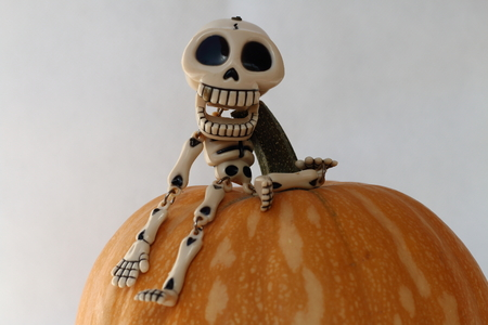 Close up to a mini skeleton on a pumpkin