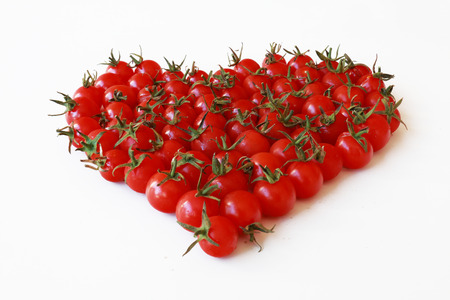 ecologically: Delicious and healthy ecologically grown cherry tomatoes, arranged in the form of heart Stock Photo