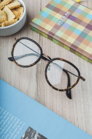 Woman glasses with planner, cookies and books