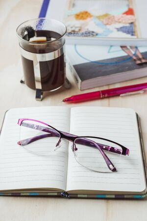 Woman glasses with notebook, coffee, pencil and book 写真素材