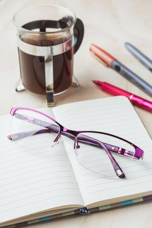 Woman glasses with notebook, coffee and pencils Stok Fotoğraf