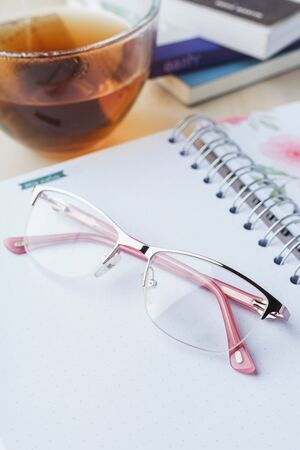 Woman glasses with notebook, tea and books