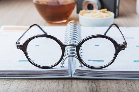 Woman glasses with planner, tea and camera