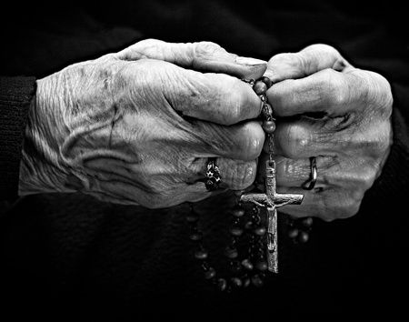 rosary: two hands holding a rosary Stock Photo