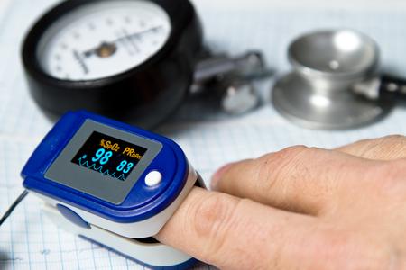 Een pulsoximeter die wordt gebruikt om polsslag- en zuurstofniveaus te meten met een bloeddrukmeter en medische stethoscoop en ECG-achtergrond Stockfoto