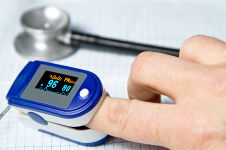 A pulse oximeter used to measure pulse rate and oxygen levels with medical stethoscope and ECG background
