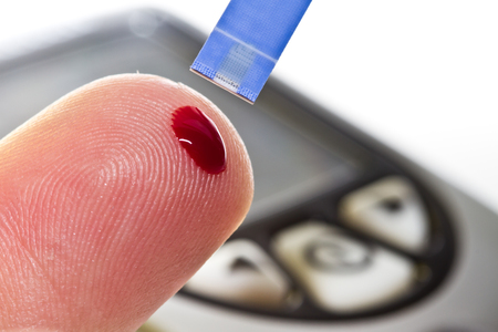 hyperglycemia: Checking the glucose level with a glucometer Stock Photo