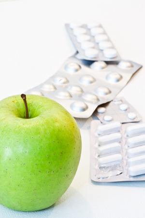 Green apple and pills isolated