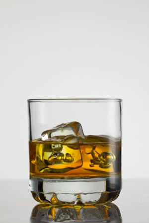 liquor glass: Glass of whisky with ice on white background