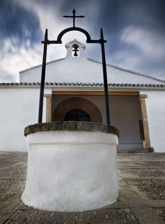 chappel: Spanish chapel with a well in the foreground and the church tower in the background. Clouds in motion