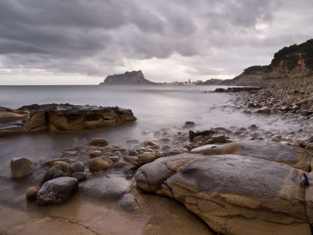 Seascape on a rocky beach with a mountain on the foreground and some rocks on the foregound Stock Photo - 5468776