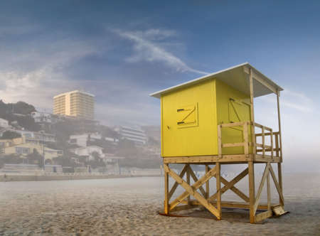 Beach scene taken in Benidorm, Costa Blanca, Spain, in a foggy day, with a yellow lifeguard stand on the foregroung photo