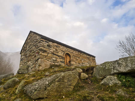 Romanesque church located in the Pyrenees, with some stones on the foreground. Horizontal composition photo