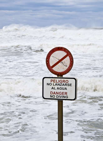 no diving sign: Danger No Diving sign with a stormy sea in the background. Signal written in Spanish and English