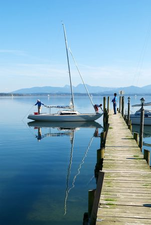 A couple prepare their sailing boat in Chiemsee lake pier Stock Photo - 7348651