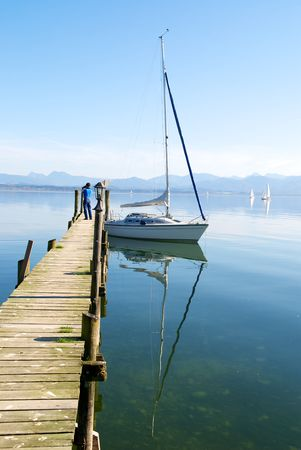 Sailing boat and reflection in Chiemsee lake pier, Germany Stock Photo - 7350754