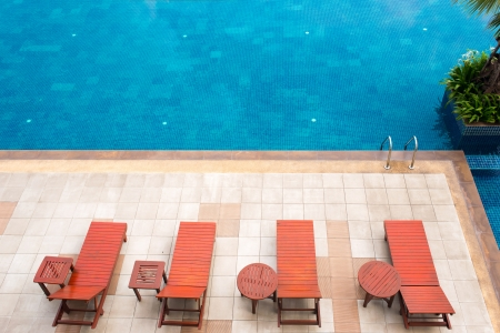 poolside deckchairs with blue swimming pool photo