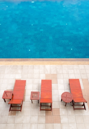 pool deck: empty poolside deckchairs with beautiful blue swimming pool Stock Photo