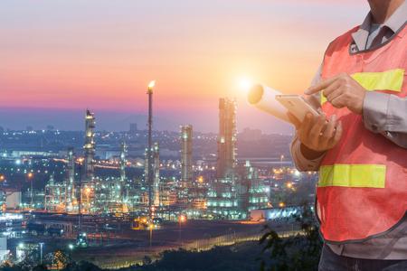 het dubbele belichtingsbeeld van de ingenieur die een smartphone-overlay met het beeld van de olieraffinaderij gebruikt. Het concept van het moderne leven, techniek, constructie en internet der dingen.