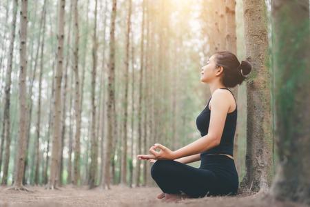 Une jeune femme se détend dans une pose de yoga dans la nature verdoyante