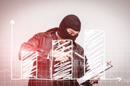 A man wearing a suit, wearing a robber, carrying a gun, ready to go out to rob,Business down concept Фото со стока
