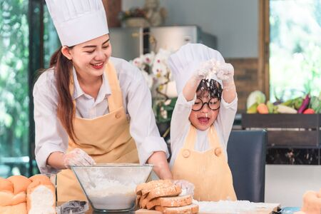 Young family cooking food in kitchen. Happy young girl with her mother mixing batter in the bowl. Stock Photo