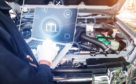 The abstract image of mechanic point to the hologram on his computer and blurred car engine room is backdrop. the concept of communication, network, insurance, financial and internet of things.