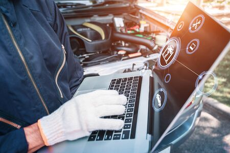 Mechanic using computer on engine background with car service icons. car service and checking concept. car insurance concept