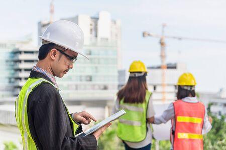 Geschäfts-, Gebäude-, Industrie-, Technologie- und Menschenkonzept - lächelnder Baumeister in Bauarbeiterhelm mit Tablet-PC-Computer über Gruppe von Bauarbeitern auf der Baustelle Standard-Bild